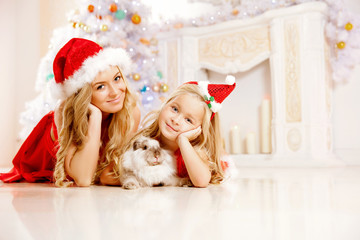 Mom and daughter dressed as Santa celebrate Christmas. Family at