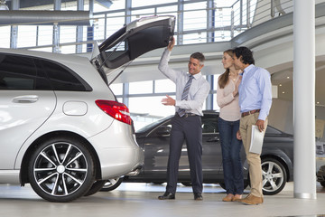 Salesman and couple looking into hatchback of car in car dealership showroom