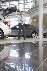 Portrait of smiling salesman with brochure leaning on hatchback door in car dealership showroom