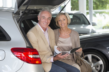 Portrait of smiling couple looking at brochure in hatchback of car in car dealership showroom