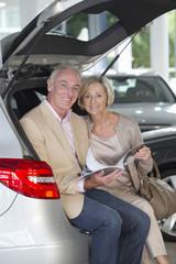 Portrait of smiling couple looking at brochure in hatchback of car in car dealership showroom