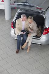Couple looking at brochure in hatchback of car in car dealership showroom