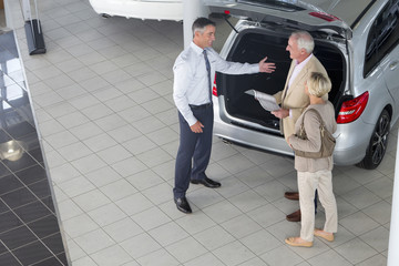 Salesman showing couple with brochure hatchback of car in car dealership showroom