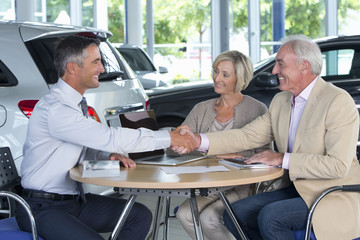 Smiling salesman and couple shaking hands at table in car dealership showroom