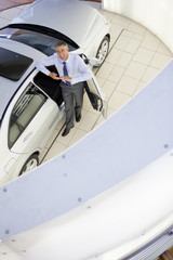 Portrait of smiling salesman leaning on car in car dealership showroom