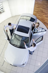 Salesman and couple looking inside car in car dealership showroom
