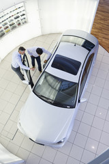 Salesman and customer looking inside car in car dealership showroom