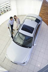 Couple looking inside car in car dealership showroom
