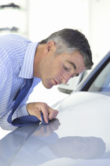 Salesman wiping automobile hood with tie in car dealership showroom