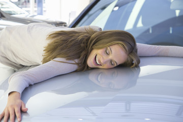 Smiling woman laying on automobile hood in car dealership showroom