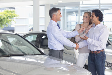 Salesman giving couple car keys in car dealership showroom