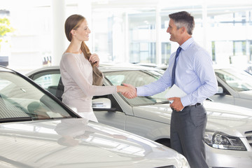 Salesman and customer shaking hands in car dealership showroom