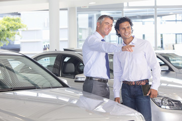 Smiling salesman showing customer cars in car dealership showroom