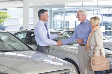 Salesman shaking hands with couple in car dealership showroom
