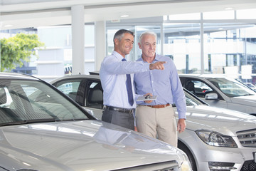 Salesman with digital tablet showing customer car in car dealership showroom