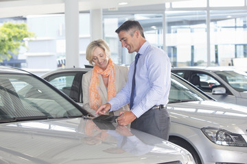 Salesman and customer looking at brochure in car dealership showroom