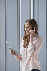 Businesswoman with headset talking on telephone and using digital tablet near window