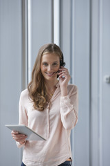 Portrait of smiling businesswoman with headset talking on telephone and using digital tablet near window