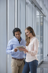 Businessman and businesswoman with headsets using digital tablet near window