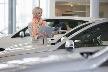 Customer looking at brochure next to car in car dealership showroom