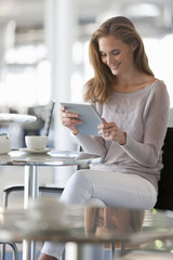 Smiling woman reading digital tablet at cafe table