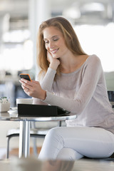 Woman checking cell phone at cafe table