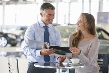 Salesman and customer looking at brochure at table in car dealership showroom