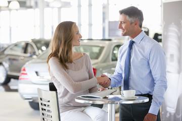Salesman and customer shaking hands at table in car dealership showroom