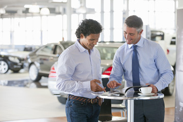 Salesman and customer viewing brochure in car dealership showroom