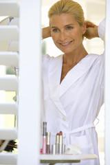 Mature woman in bathrobe adjusting hair, smiling, view through shutters