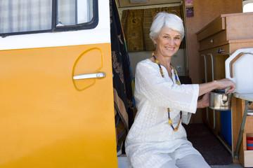 Senior woman making tea in camper van, smiling, portrait