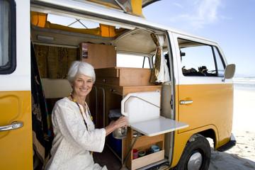 Senior woman making tea in camper van on beach, smiling, portrait, close-up