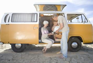 Senior couple making tea in camper van on beach
