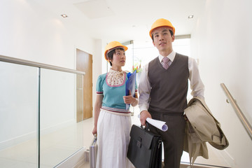 Young businessman and woman in hard hats in office, woman looking at man, low angle view,