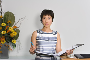 Young female receptionist with folder by flower arrangement, portrait