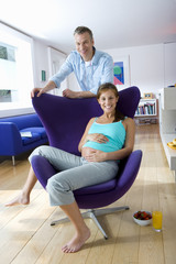 Man by pregnant woman in armchair, smiling, portrait,