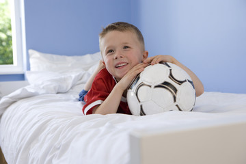 Boy (4-6) lying on stomach on bed resting chin on football, smiling