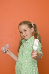Girl (9-11) with light bulbs by orange wall, smiling, portrait