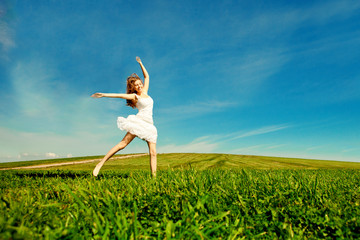 Woman jumping. Young beautiful girl jumping in  field on the gra