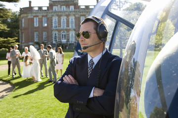 Helicopter pilot in sunglasses by helicopter, wedding party in background
