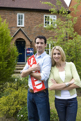 Young couple outside house, man with 'sold' sign, smiling, portrait