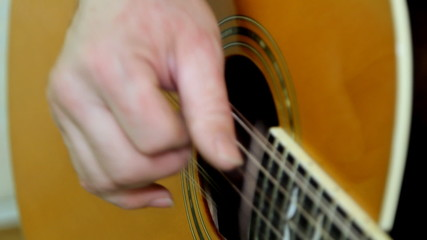 performer playing on the acoustic guitar