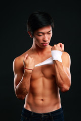 Boxer preparing for a fight bandaging his hands