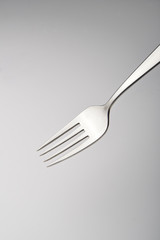 Close up of a silver fork on grey gradient background