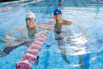 Male swimmers in swimming pool, smiling, portrait