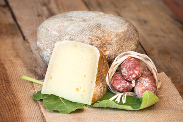 Pecorino cheese with wild boar sausage, and a fig leaf on a wood
