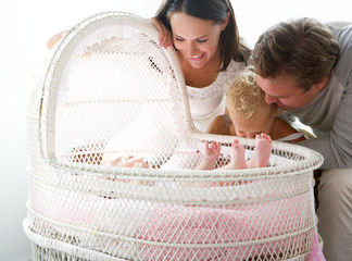 Young family smiling at baby in cot