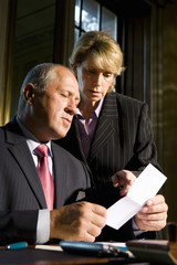 Businesswoman showing businessman paperwork, low angle view