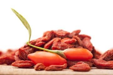 pile of dry and fresh goji berry on white background