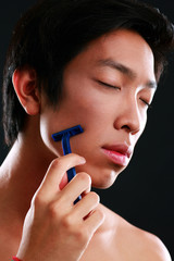 Asian man shaving on black background